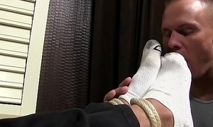 Hunk ties up his buddy and licks his toes while jerking off