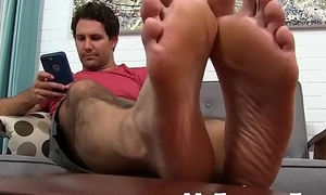 He loves cock teasing with his feet while on his phone